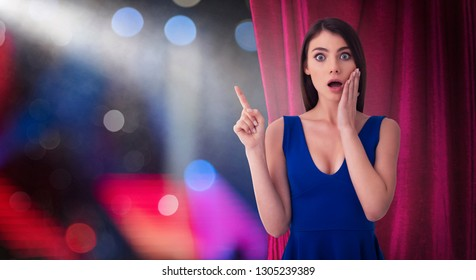 Pretty woman in front of red curtains indicates something about the theater show