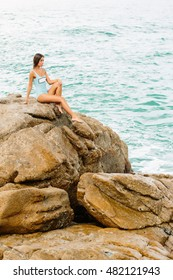44ee2a4ef579 Pretty woman in full body swimsuit with long healthy hairs sit on big stone  on the