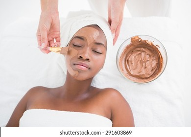 Pretty woman getting a chocolate facial treatment at the health spa