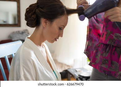 A pretty woman getting her hair styled and blow dried.
