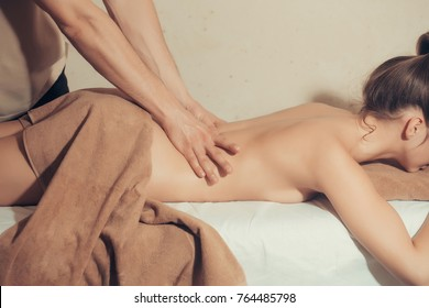 pretty woman or girl with sexy body and male hands of masseur therapist makes massage in beauty spa salon