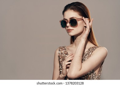 pretty woman in golden dress and sunglasses model