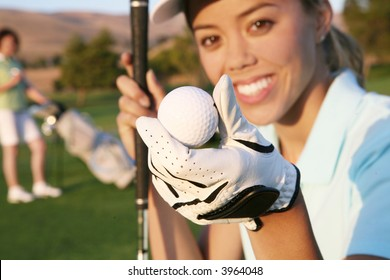 A pretty woman golfer holding a golf ball