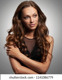 pretty woman with gorgeous long curly brown hair. Studio shot