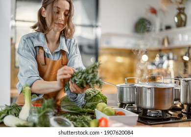 Pretty woman with green ingredients and spicy herbs cooking healthy food on the kitchen. Healthy and wellness concept. High quality photo