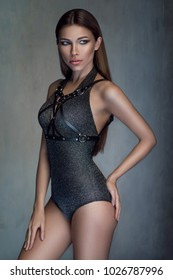 Pretty woman in grey bodysuit and harness posing at camera in studio