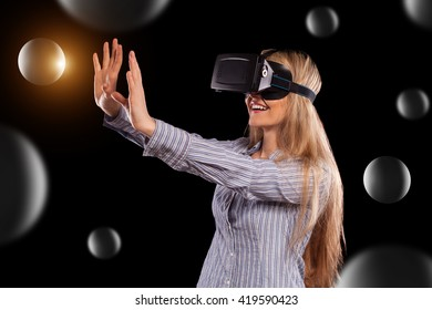 Pretty woman in grey shirt touching something curiously using the virtual reality headset on black background.