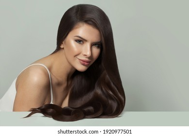 Pretty woman hair model with long healthy hairstyle on white background. Haircare and facial treatment concept