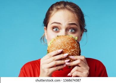 pretty woman with hamburgers in hands in red t-shirt, fast food delicacy