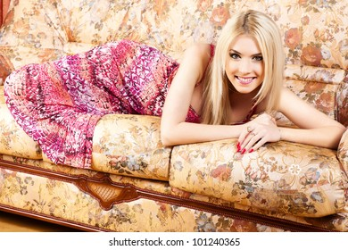 The pretty woman has relaxed on a sofa.
