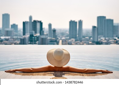 Pretty woman in hat relax in swimming pool on roof top enjoy cityscape panorama view. Vacation, summer and relax concept