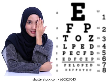 Pretty woman having eye test at ophthalmologist office with blurry word background