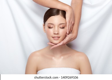 pretty woman having facial massage with her eyes closed, young and fresh female in spa, beauty theraphy, copy space