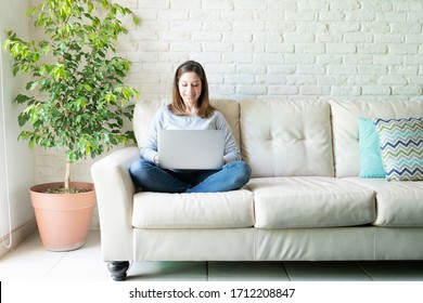 Pretty woman in her 40s dressed casual and using a laptop computer while sitting in a couch at home