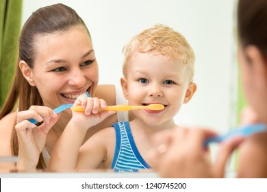 Pretty woman and her child son brushing their teeth and looking at miroor in bathroom