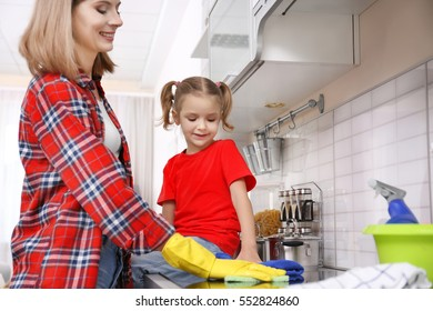 Pretty woman and her daughter washing electric stove at home
