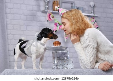 Pretty woman with her dog having pet birthday party