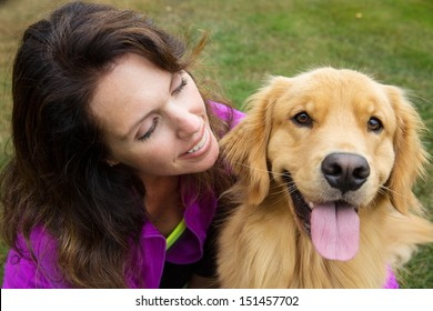 A pretty woman and her golden retriever dog