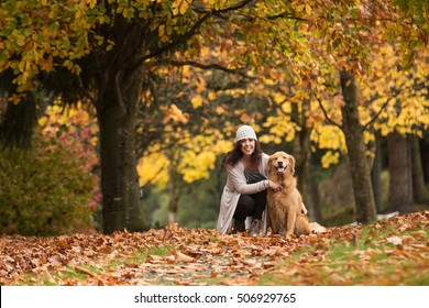Pretty woman with her Golden Retriever Dog at a park in the Fall