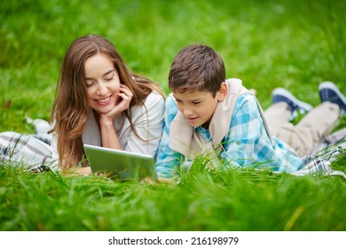Pretty woman and her son using digital tablet outdoors