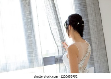Pretty woman with her wedding dress before leaving for the Church