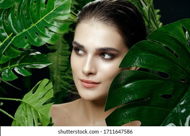 Pretty woman hid in the green leaves of a palm tree