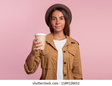 Pretty woman holding a cup of coffie in the hand and smiles to camera, isolated over pink