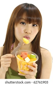 Pretty woman holding cup of eating slice of tropical fruit