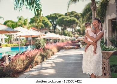 Pretty woman holding little daughter in her arms. First vacation time together with baby.