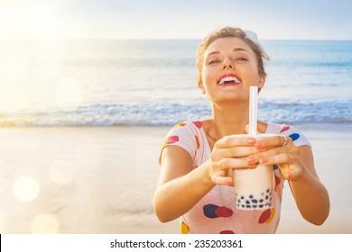 pretty woman holding modern asian beverage (bubble tea) on a beach