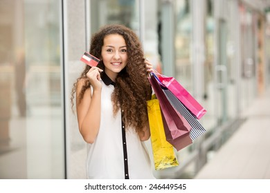 Pretty woman holding shopping bags and showing blank credit card, against mall background