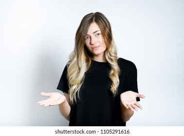 Pretty woman holding something invisible and big in her palms with copyspace area on gray background