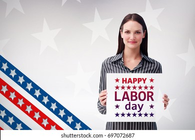 Pretty woman holding a white sheet of paper against digital image of american flag