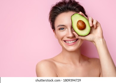 Pretty woman holds half an avocado in front of her face. Photo of attractive woman with perfect makeup on pink background. Beauty & Skin care concept