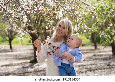 pretty woman holds in her arm boy.  Spring the wonderful flowering period for almonds on nature. feeling of tenderness, love, care and fun, and caring joy