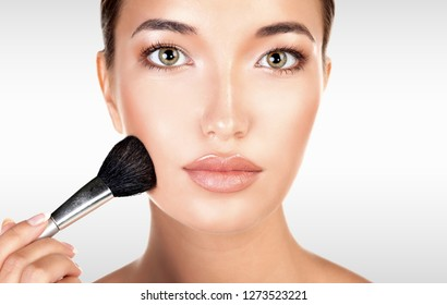 Pretty woman holds makeup brush against a grey background with copyspace