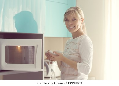 Pretty Woman at home using microwave oven.