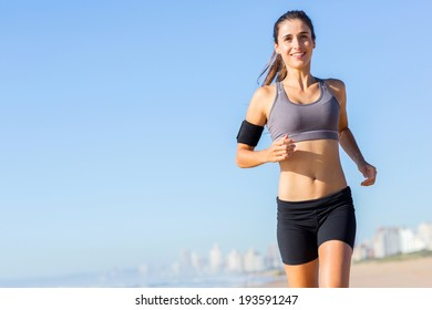 pretty woman jogging on the beach in the morning