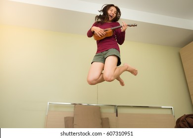 Pretty woman jumping with ukulele on her bed