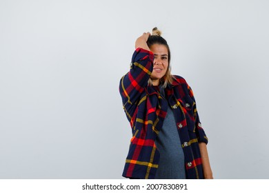 pretty woman keeping hand on head in casual clothes and looking jovial. front view.