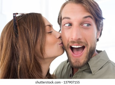 Pretty woman kissing man with beard on the cheek