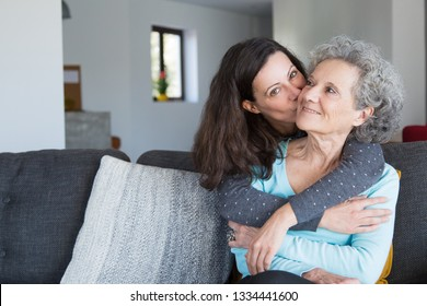 Pretty woman kissing senior mother and hugging her from back. Smiling elderly lady spending time with young daughter. Bonding concept