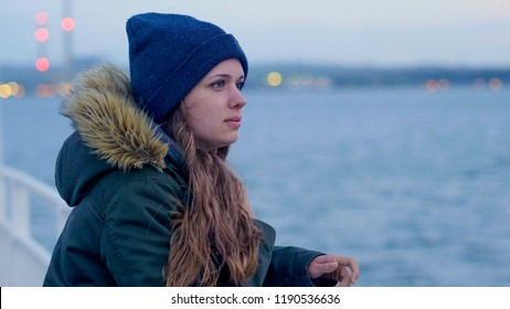 Pretty woman leans on the reeling of a boat