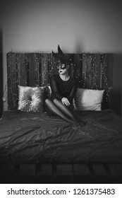 Pretty woman in leather rabbit mask laying on a bed