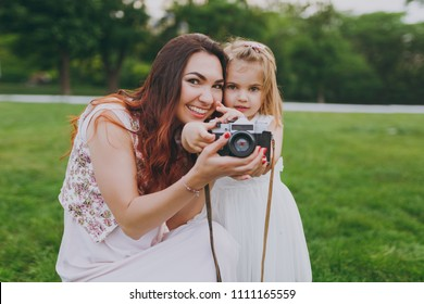Pretty woman in light dress and little cute child baby girl take picture on retro vintage photo camera in park. Mother, little kid daughter. Mother's Day, love family, parenthood, childhood concept