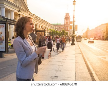 Pretty woman in light suit with drink in hand travels to the city against the setting sun. Russia. Sankt-Peterburg. Nevsky prospekt.