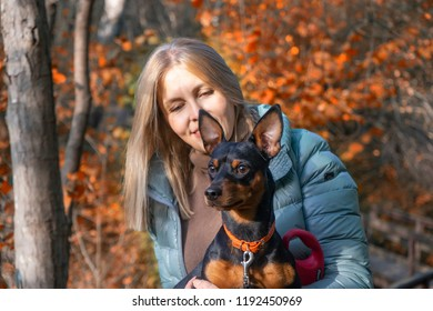 Pretty woman with little dog in autumn park