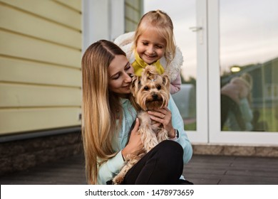 pretty woman with long blonde hair holding small dog yorkshire terrier outdoor, next sitting little girl. Happy Mother and daughter with pet on backyard. Family concept