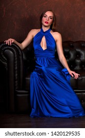 Pretty woman in long blue gown sitting on a leather sofa