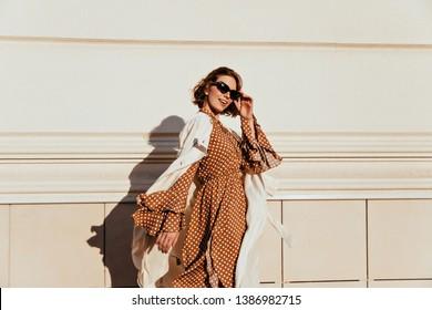 Pretty woman in long brown dress enjoying sunny day. Lovable white girl in retro attire walking down the street.